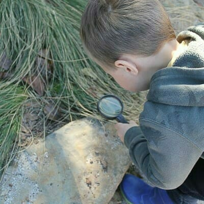 Boy investigating with magnifying glass